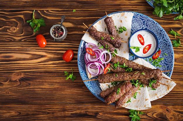 Turco e árabe tradicional ramadan misturam prato de quibe. kebab adana, frango, cordeiro e carne no pão lavash com molho. vista do topo Foto gratuita