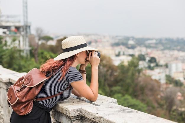 Turismo feminino com câmera na varanda Foto gratuita
