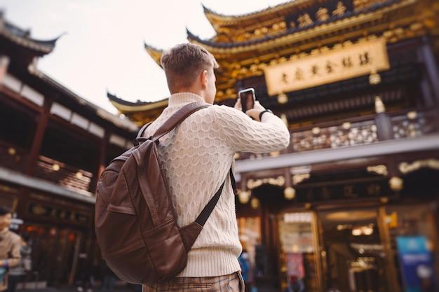 Turismo masculino tirando fotos de um pagode no mercado de yuyuan em xangai Foto gratuita