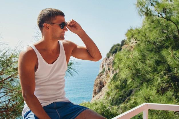 Turismo, o lazer é um homem bonito, se aquecendo no vestido branco na varanda do hotel com vista para plantas tropicais e mar Foto Premium
