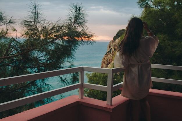 Turismo, recreação - uma linda garota com cabelos longos, de pé em um jaleco branco na varanda do hotel com vista para o mar e o pôr do sol Foto Premium