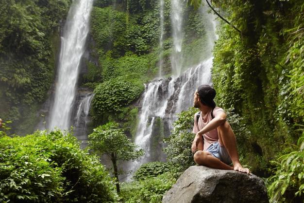 Turismo, viagens e aventura. jovem hippie estiloso sentado na pedra com os pés descalços e virando a cabeça para trás para ver uma cachoeira incrível Foto gratuita