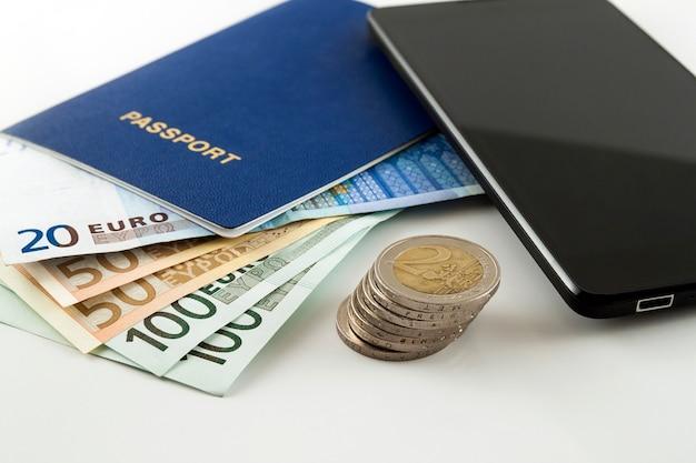 Turismo, viagens e objetos, dinheiro do euro, smartphone e passaporte itinerante em fundo branco mesa Foto Premium
