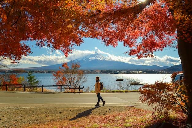 Turista admirando o monte. fuji no outono, temporada de outono colorida e montanha fuji com manhã e folhas vermelhas no lago kawaguchiko é um dos melhores lugares do japão Foto Premium