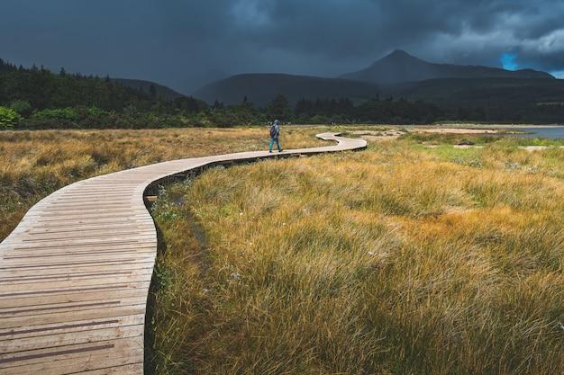 Turista andando no caminho de madeira. irlanda. Foto Premium