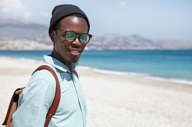 Turista atraente homem negro elegante, vestida com roupas da moda e acessórios posando contra água azul e areia branca Foto gratuita