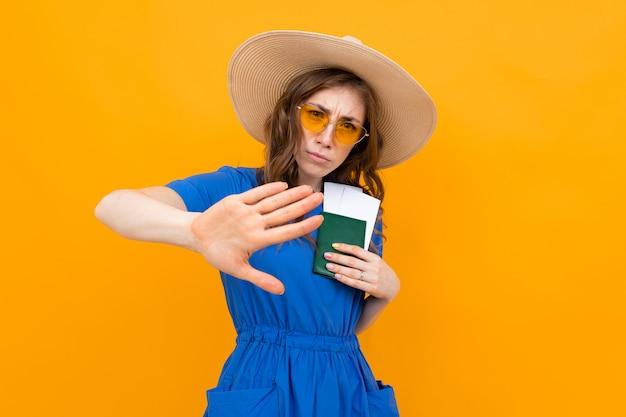 Turista com um passaporte e bilhetes em suas mãos em um fundo amarelo, um gesto mostra caindo atrás dela Foto Premium