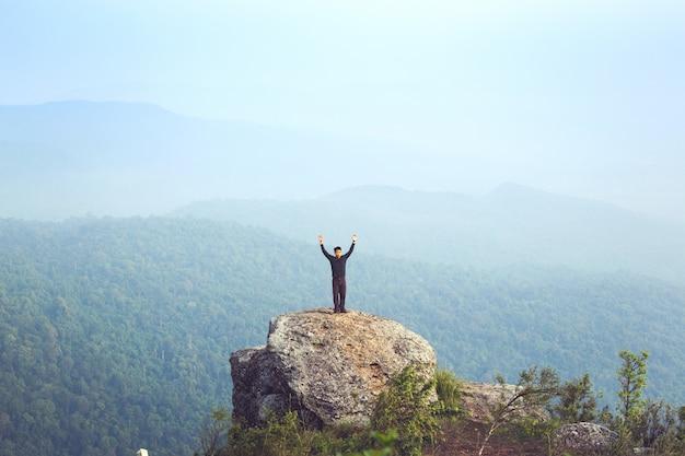 Turista de ásia do homem novo na montanha está olhando sobre o nascer do sol da manhã enevoada e nevoenta Foto Premium