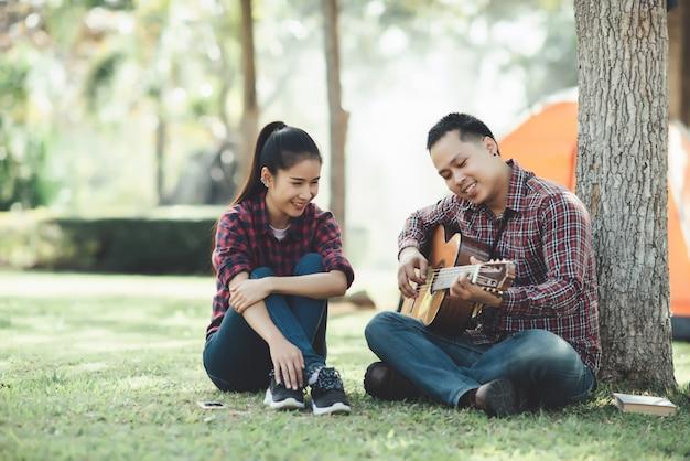 Turista de casal apaixonado por tocar violão na natureza Foto gratuita