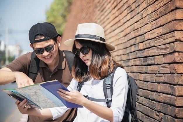 Turista de casal asiático segurando o mapa da cidade Foto gratuita