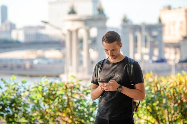 Turista de homem com smartphone e mochila na rua europa. Foto Premium