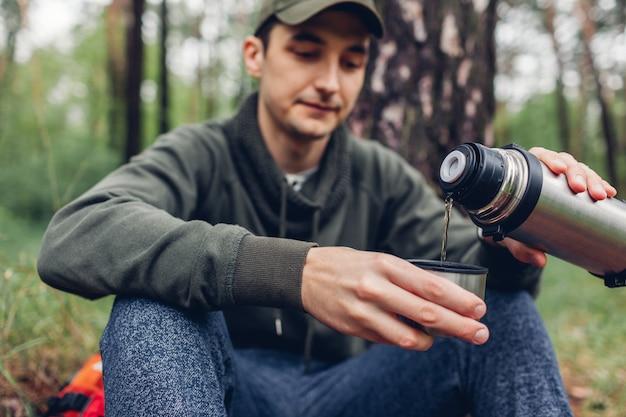 Turista de homem derrama chá quente fora da garrafa térmica na floresta de primavera camping, viajando Foto Premium