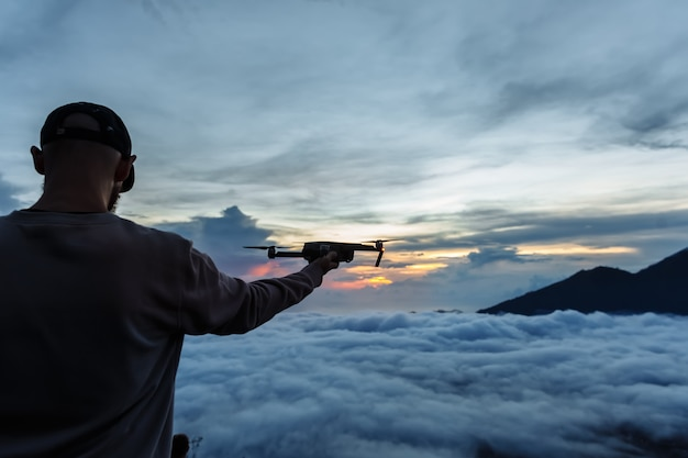 Turista de homem olha para o nascer do sol no vulcão batur, na ilha de blai, na indonésia. alpinista homem lançando um avião voando com um controle remoto na mão, conceito de viagens Foto Premium