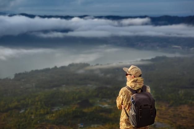 Turista de homem olha para o nascer do sol no vulcão batur, na ilha de blai, na indonésia. homem alpinista com mochila viajar no topo do vulcão, conceito de viagens Foto Premium