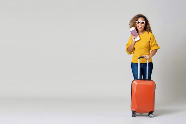 Turista de mulher afro-americana com bagagem segurando o passaporte e o cartão de embarque Foto Premium