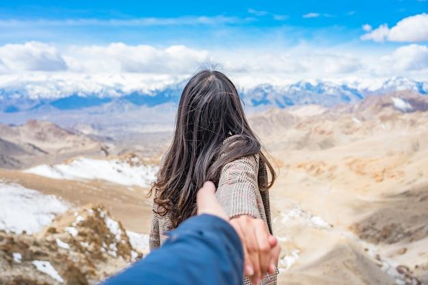 Turista de mulher jovem asiática usando casaco levando o homem em vista da montanha do himalaia, contra o céu azul Foto Premium
