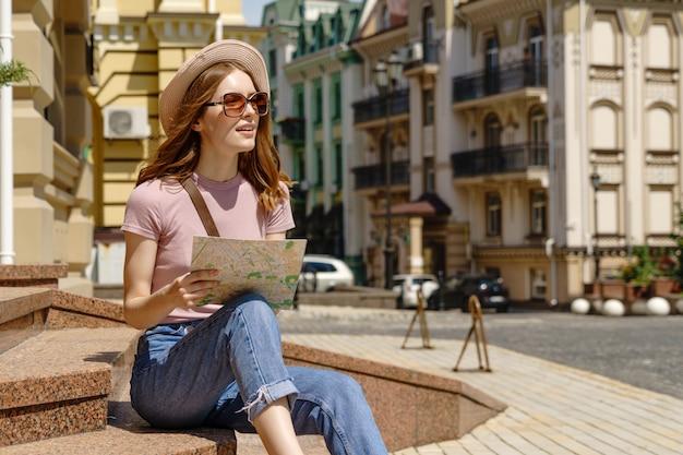 Turista de mulher jovem e bonita agradável com mapa da cidade, sentado nas escadas no centro da cidade. Foto Premium