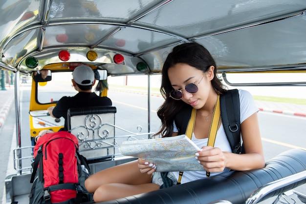 Turista de mulher viajando no táxi de tuk tuk local em bangkok tailândia Foto Premium