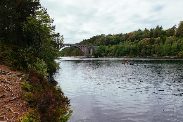 Turista de remo do barco no lago com paisagem verde Foto gratuita
