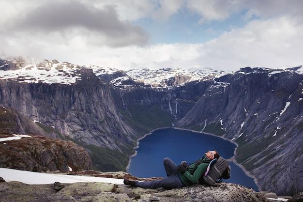 Turista descansa antes de uma linda vista sobre o lago da montanha em algum lugar da noruega Foto gratuita