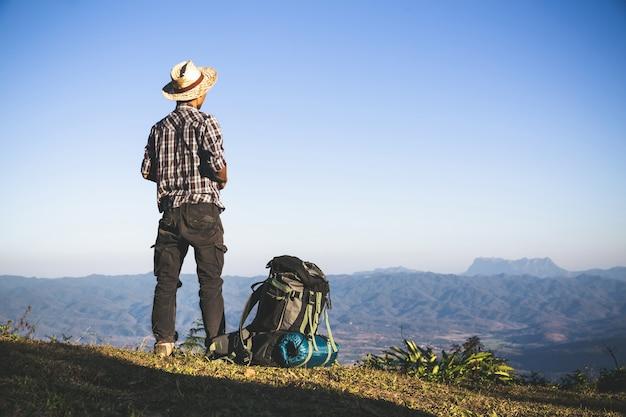 Turista do topo da montanha. raios solares. homem usar mochila grande contra a luz do sol Foto gratuita