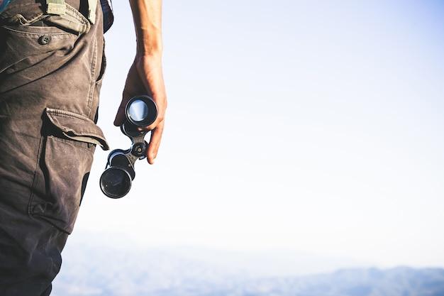 Turista está segurando através de binóculos no céu nublado ensolarado do topo da montanha. Foto gratuita