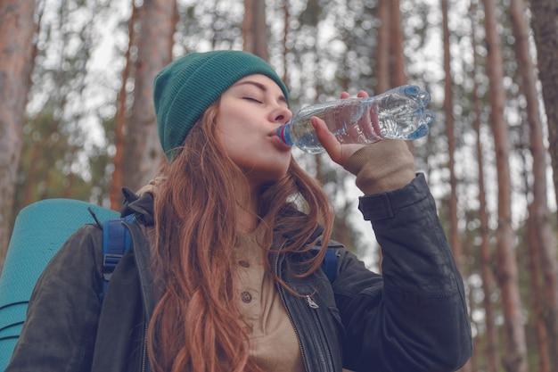 Turista feliz da mulher com água potável da trouxa da garrafa na natureza. Foto Premium