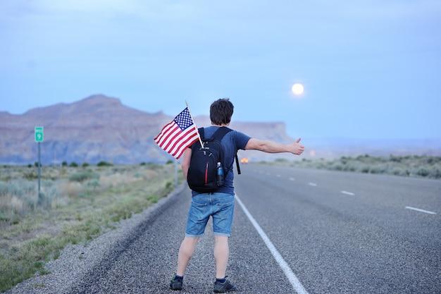 Turista masculina da idade média com a bandeira americana na trouxa que viaja ao longo de uma estrada desolada Foto Premium