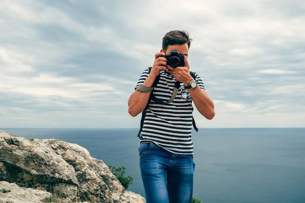 Turista masculino fotógrafo com uma câmera digital profissional e lente Foto Premium