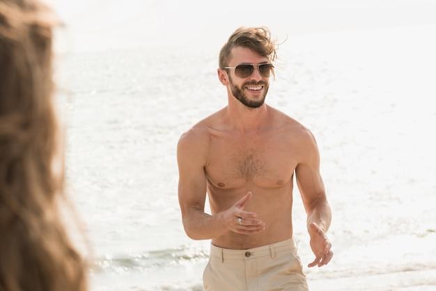 Turista muscular sem camisa, andando na praia no verão Foto Premium