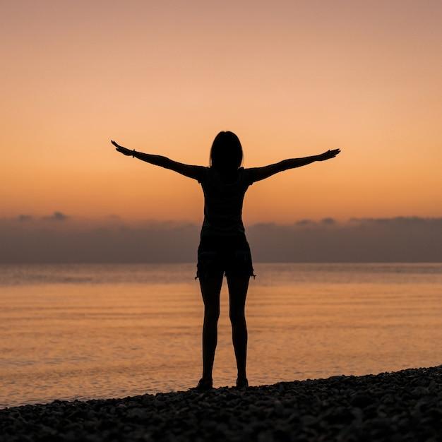 Turista no nascer do sol, segurando as mãos no ar Foto gratuita