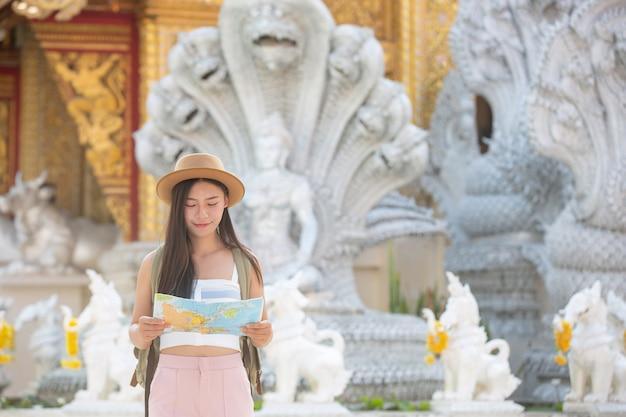 Turistas do sexo feminino segurar um mapa para encontrar lugares. Foto gratuita
