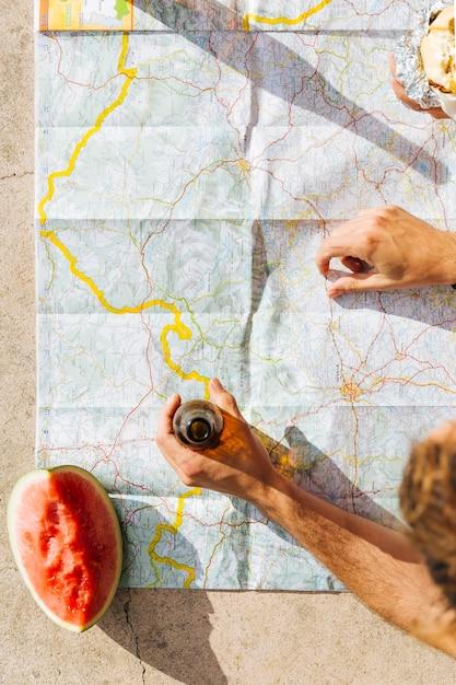 Turistas encontrar caminho no mapa de papel Foto gratuita