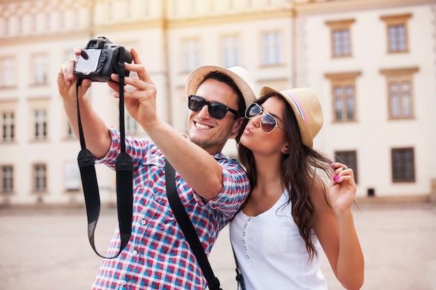 Turistas felizes tirando fotos de si mesmos Foto gratuita