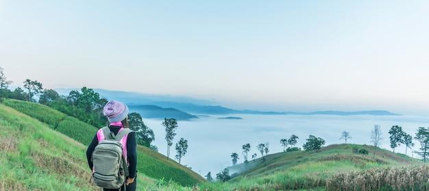 Turistas fêmeas de ásia que estão, olhando o cenário da montagem e o nascer do sol da manhã. Foto Premium