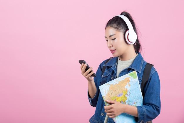 Turistas fêmeas no estúdio em um fundo cor-de-rosa. Foto gratuita