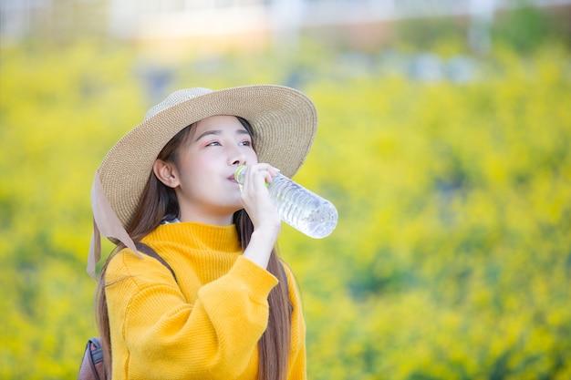 Turistas femininos ficam bebendo água enquanto caminhava. Foto gratuita