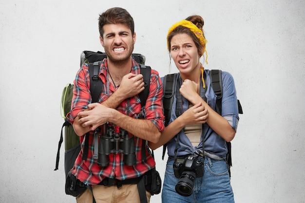 Turistas masculinos e femininos infelizes com mochila, câmera e binóculos, coçando as mãos com cuidar infeliz depois de andar na floresta profunda. pessoas, aventura, conceito de viagem Foto gratuita