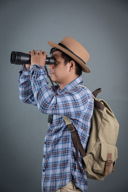 Turistas masculinos que backpacking guardarando o fundo cinzento dos binóculos. Foto gratuita