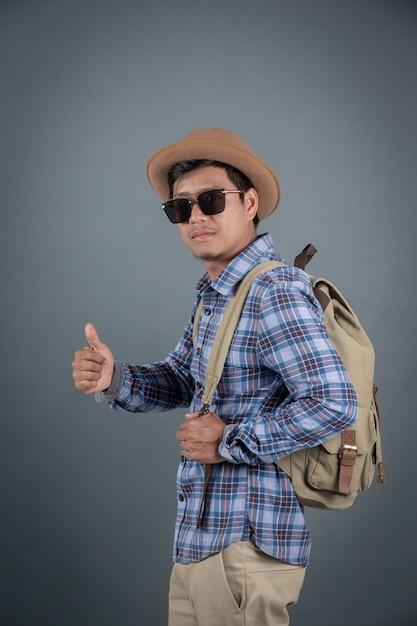 Turistas masculinos que backpacking o fundo cinzento. Foto gratuita