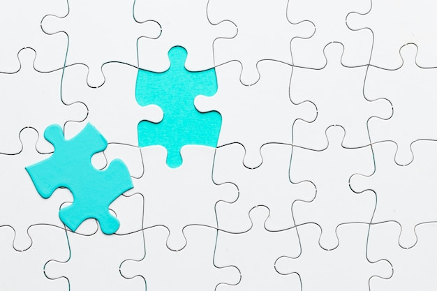 Turquesa pedaço de quebra-cabeça no cenário de quebra-cabeça branca Foto gratuita