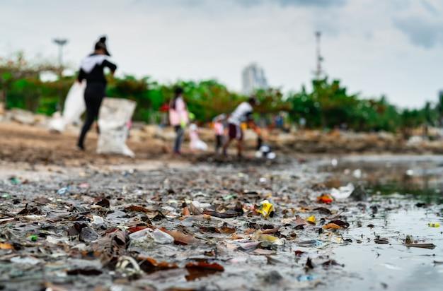 Turva de voluntários coletando lixo. poluição do ambiente de praia. Foto Premium