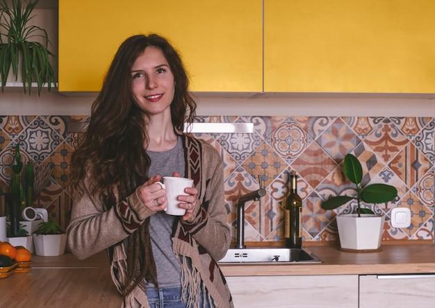 Turva linda sorridente saudável jovem segurando a taça e sorrindo na cozinha Foto Premium