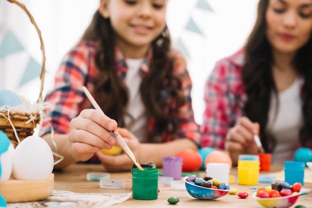 Turva mãe e filha pintando os ovos de páscoa por cima da mesa Foto gratuita