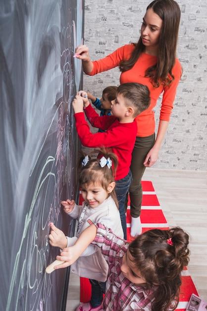 Tutor feminino desenhando na lousa com crianças Foto gratuita