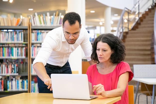 Tutor que explica a pesquisa específica do aluno na biblioteca Foto gratuita