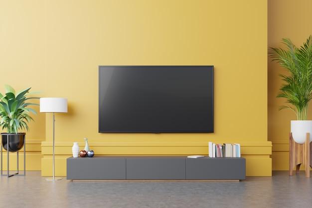 Tv no armário na moderna sala de estar com lâmpada, mesa, flor e planta no fundo da parede amarela. Foto gratuita