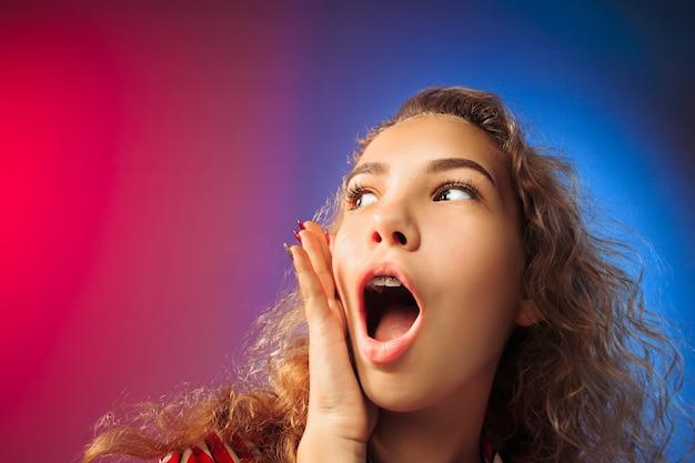 Uau. belo retrato frontal feminino com metade do comprimento em backgroud do estúdio vermelho e azul. jovem emocional surpresa mulher em pé com a boca aberta. emoções humanas, conceito de expressão facial. Foto gratuita