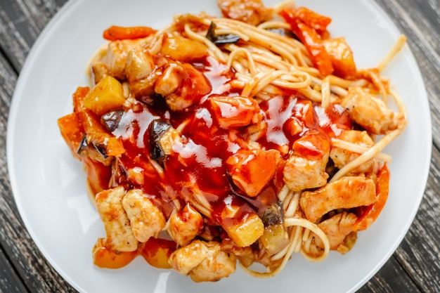 Udon frite o macarrão com frango e legumes em molho agridoce. cozinha asiática tradicional Foto Premium