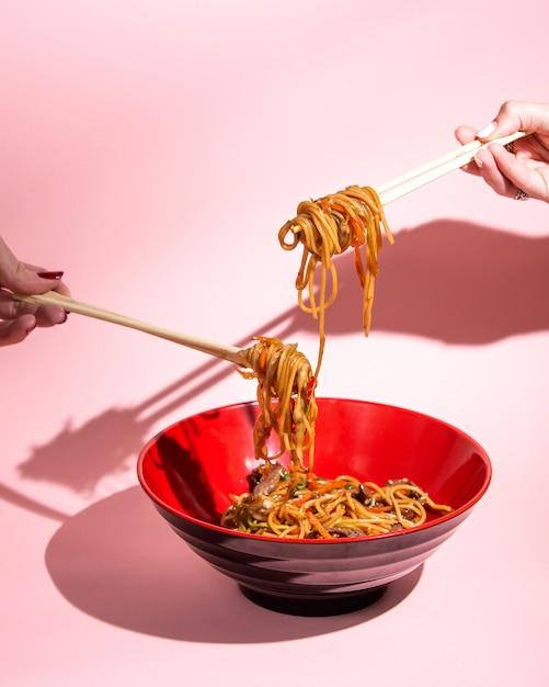 Udon misture macarrão frito com carne pimentão cebolinha molho de soja e gergelim em uma tigela Foto gratuita